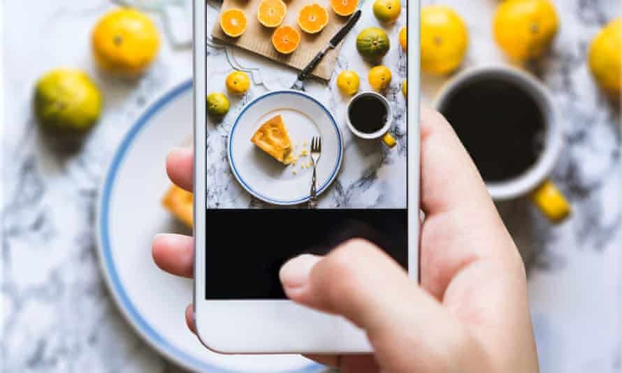An iPhone taking a picture of a home-made cake