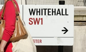 Pedestrian walks past a sign on Whitehall