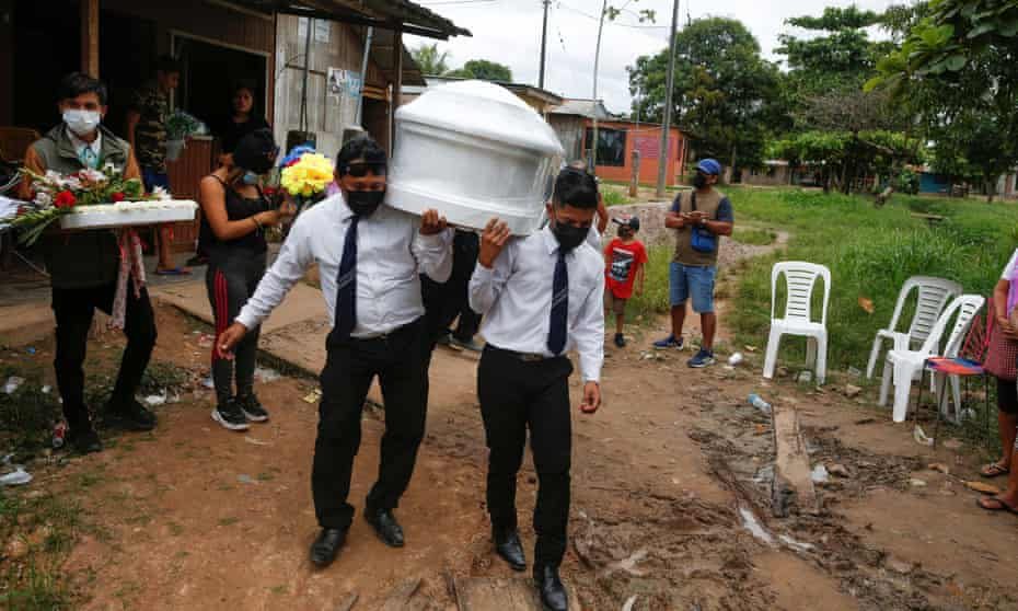 Funeral home workers carry the coffin of a coronavirus victim in Pucallpa, Peru.