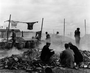Freed prisoners scavenging in the rubbish dump, Dachau, Germany, 1945.   Lee Miller wrote: 'Prisoners were prowling these heaps, some of which were burning, in the hope of finding something more presentable than what they were wearing already'