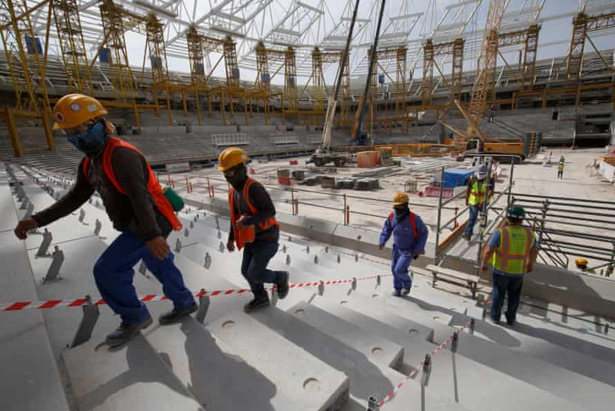 Workers walk up into the stands at the construction site for the al-Rayyan stadium.