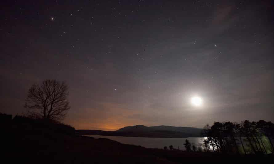 A clear sky at night over Clatteringshaws Loch