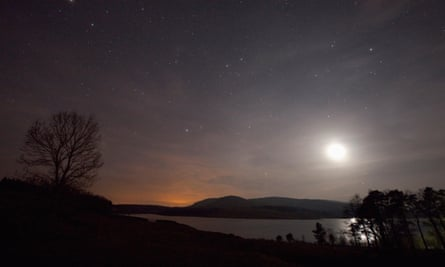 A clear sky at night over Clatteringshaws Loch, Galloway Forest Park, Dumfries and Galloway, Scotland.
