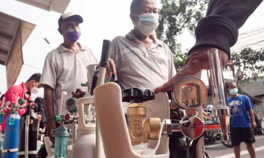 People wait in line to refill their oxygen tanks at a filling station in Jakarta