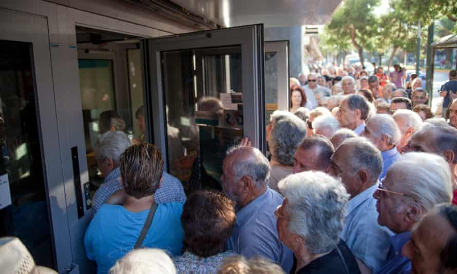 Greek people queue to enter a bank