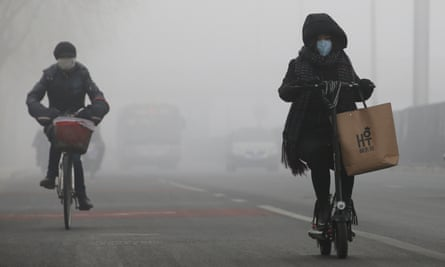 People cycle in the smog in Beijing.