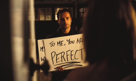 Still from Love Actually - man (played by Andrew Lincoln) shows 'To me you are perfect' poster to woman