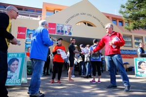 Fresh from the surf, a Manly voter drops into Queenscliff surf life saving club to cast his ballot – but not without some last-minute campaigning from the Labor team
