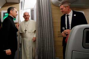 Pope Francis, his spokesperson Matteo Bruni (right) and his trip organiser, Father Mauricio Ruedaand (left), greet journalists onboard his plane before arriving in Bangkok