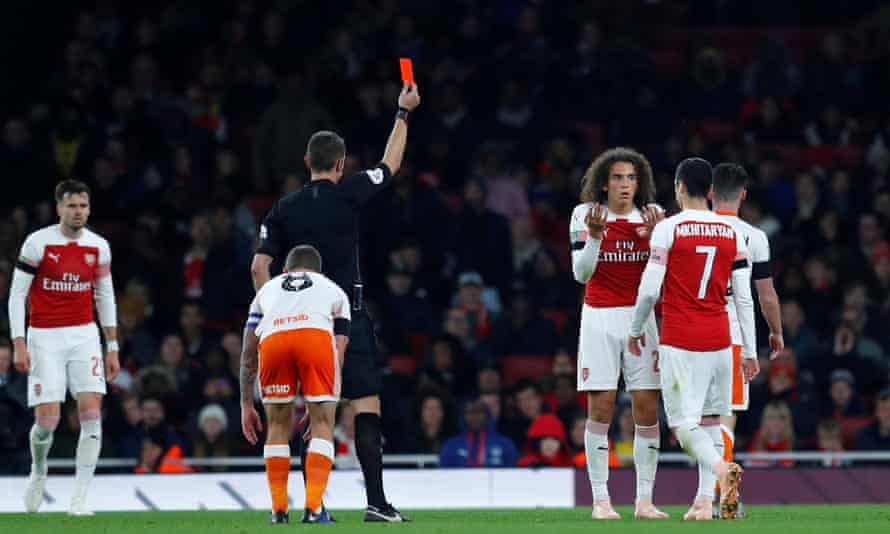 Arsenal's Mattéo Guendouzi is shown a red card by referee David Coote after collecting two yellow cards.
