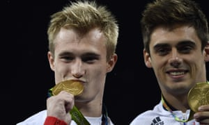 Great Britain's Jack Laugher, left, and Chris Mears, right, check their gold medals for the men's synchronised 3m springboard.