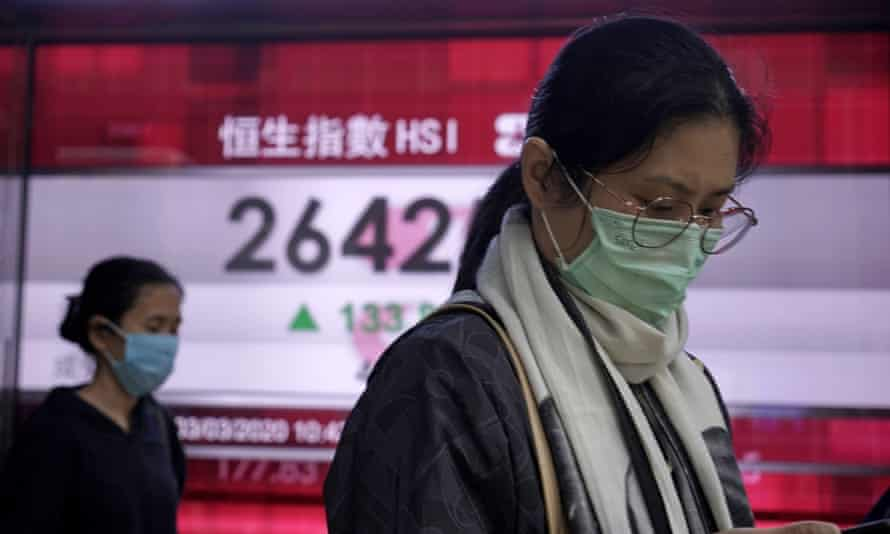 People walk past an electronic board showing Hong Kong share index outside a local bank