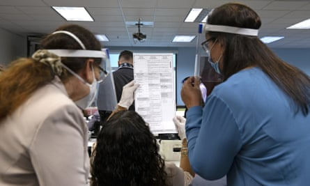 Miami-Dade elections employees and campaign observers inspect ballots and count them by hand in a manual recount for state senate 37 in Florida on 12 November.