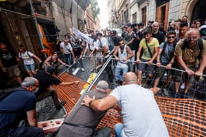 Rome, ItalyProtesters tear down a barricade during a demonstration against the 'green pass', a document proving its carrier has received a vaccine against Covid-19, which will be needed to gain entry to several venues from next month