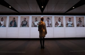 A visitor looks at photographs in the Face To Face exhibition