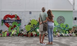 A couple look at tributes left at a memorial wall by Grenfell Tower a year after the disaster.
