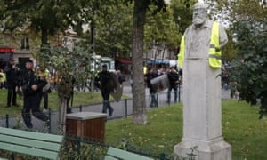 French riot police walk past a statue bearing a gilet jaune during a protest in Paris on Saturday.