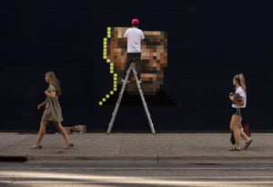 Minneapolis, Minnesota, US: artist Eric Rieger, also known as HOTTEA, works on an art installation called Pure Imagination outside the Guthrie Theater. The artwork, a portrait of George Floyd, is formed by placing hundreds of individually painted magnets on the metal exterior of the theatre