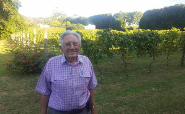 The Cedar Creek Winery managing director, John Penglis, in his vineyard, with the bore and tanks set aside for groundwater to sell to Coca-Cola in the background to the right