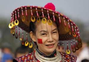 A performer in a minority ethnic costume looks on during a rehearsal before the military parade.