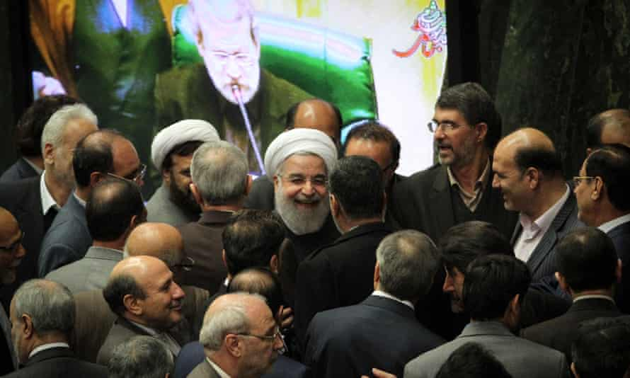 Iranian president Hassan Rouhani (center) talks with lawmakers during a session in parliament.