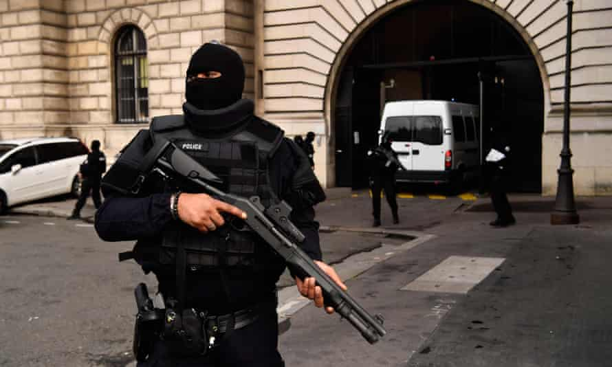 Armed police stand guard as a van carrying Jawad Bendaoud arrives at the courthouse.