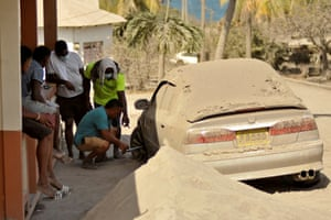 Orange Hill, Saint Vincent and the Grenadines. A man fixes a flat tyre on a car covered in ash after a series of eruptions from La Soufriere volcano