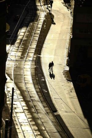 Pedestrians walk across an empty street