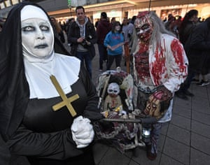 A couple dressed in Halloween costumes pose for a photo before the zombie walk in Essen, Germany.