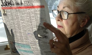 A woman reading her local newspaper.