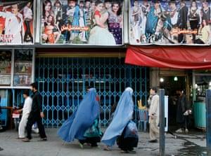Afghan women walk past a cinema in Kabul, Afghanistan.