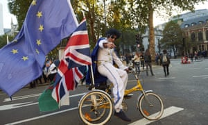A man dressed as Elvis cycles on a tricycle with European Union, Union Jack and Welsh flags.