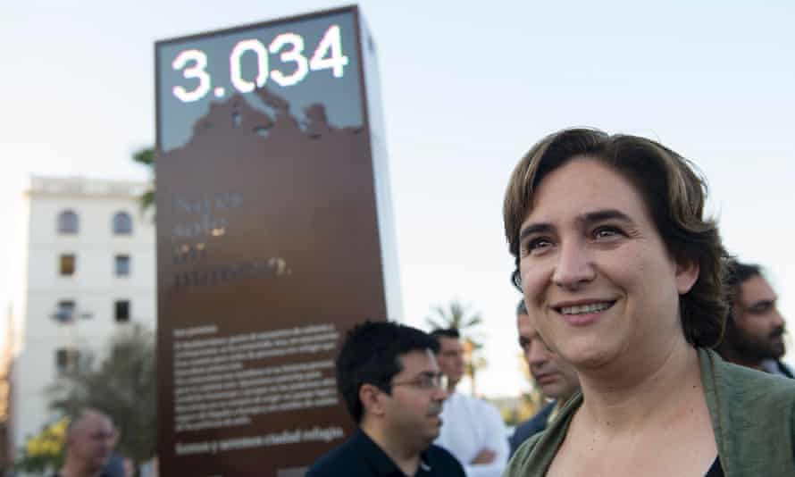 Barcelona's mayor Ada Colau poses in front a digital billboard that shows the number of refugees who died in the Mediterranean.