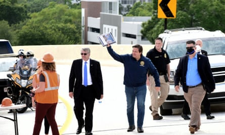 Governor Ron DeSantis waves as he and the Florida department of transportation secretary, Kevin Thibault, left, to open a new interchange in Orlando in May.