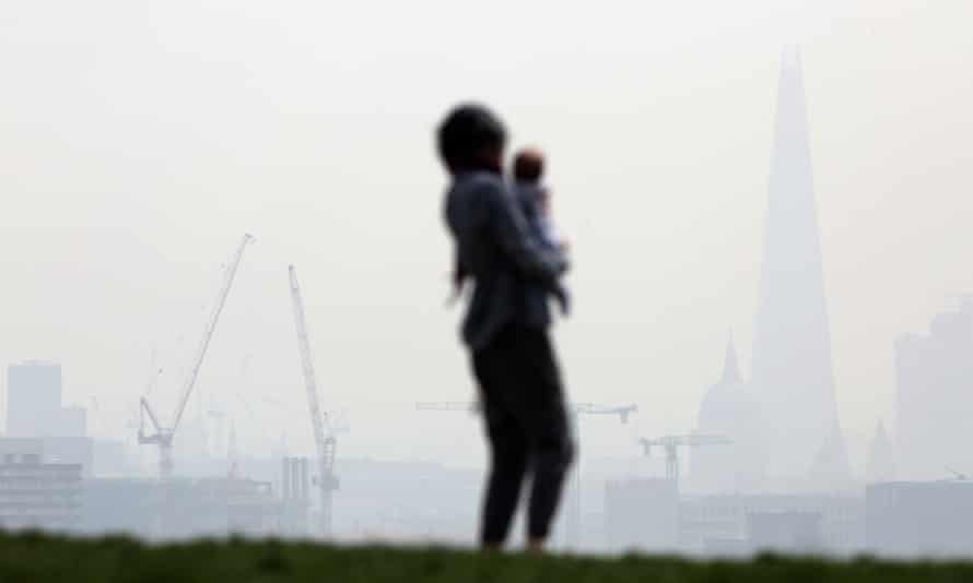 A woman and a child stand on Parliament Hill in Hampstead Heath overlooking a smoggy central London in April 2015.
