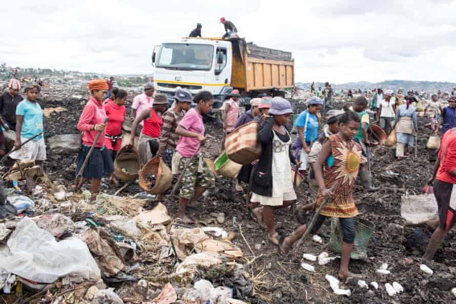 Workers rush to the next lorry dumping its load at the site.