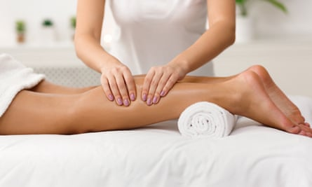 Massage therapist massaging a woman's calves in spa, side view