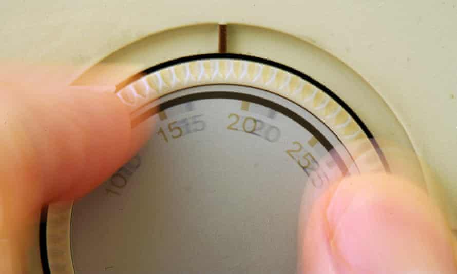 hand adjusting heating thermostat