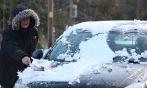 A man scrapes snow off his car in Tomintoul, in the Highlands