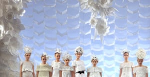 Models in white floral headwear pose against a dreamy backdrop for Chanel's Spring/Summer 2009 Haute Couture collection show