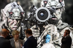 London, UKVisitors talk in front of a stand on the second day of the DSEI arms fair at ExCeL in London's Docklands