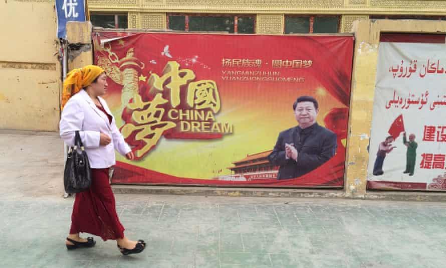 A Muslim Uighur woman in Xinjiang passes a propaganda poster celebrating the 'China Dream' of president Xi Jinping.