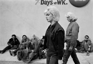 A pair of 'Old Ladies,' the girlfriends of a Hells Angels motorcycle club members, walk past bikers seated on the ground outside the Blackboard Cafe, Bakersfield, California, 1965.