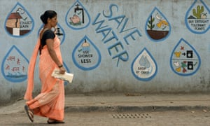 A pedestrian walks past a wall adorned with water conservation messages in Mumbai.