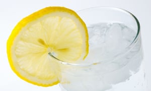 A juicy lemon perched on the side of a glass full of gin and tonic