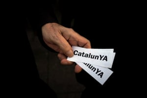 A protester holds stickers with the play-on-words slogan CatalunYA (Catalonia now) during a protest in the Puerta del Sol public square