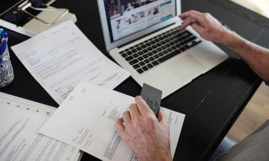 Image of man with bills doing online payment at home