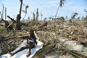 A woman sits next to her destroyed house in Les Cayes