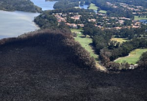 Golfers are seen on the green next to a bushfire-damaged area in Peregian Springs on the Sunshine Coast on 10 September 2019.