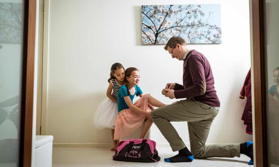 Mike Dwyer helps his eldest daughter Piper with her jazz shoes before a dance lesson